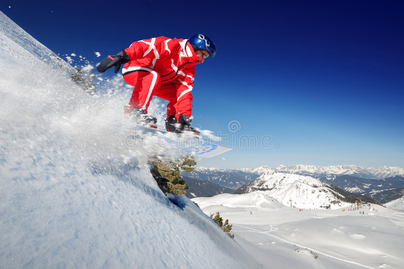Skier. Snowboarder jumping from deep powder stock images