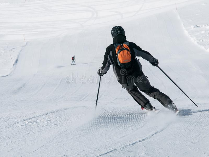 Skier in black downhill skiing on a ski slope. View from back royalty free stock image