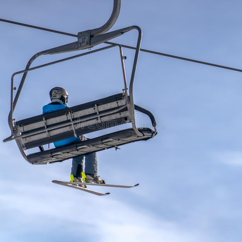 Skier on a chair lift against beautiful blue sky stock image