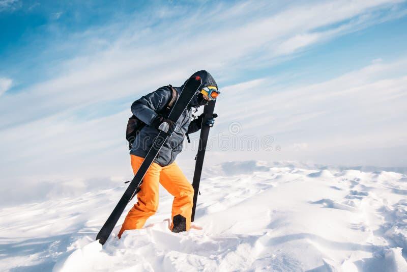 Skier climbing on snowy mountain summit. Skier climbing walking on snowy mountain summit royalty free stock photos