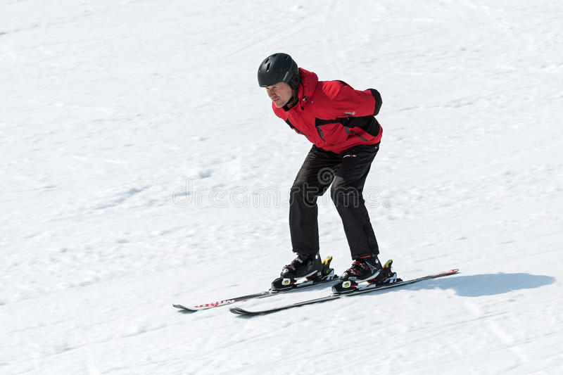 Skier coming down the slope without ski sticks. MOROZNAYA MOUNTAIN, YELIZOVO, KAMCHATKA, RUSSIA - APR 17, 2015: Skier in red and black outfit coming down the royalty free stock photo