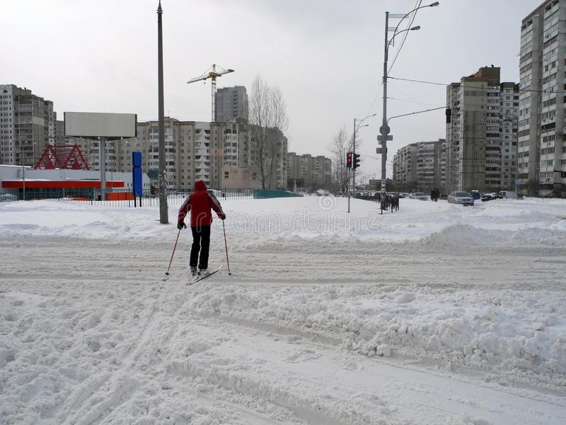 Skier crossing the road in the city. Skiing in the town Kiev. royalty free stock image