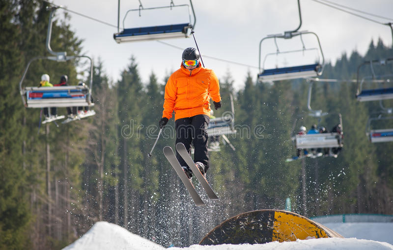 Skier flying over a hurdle in winter day. With forest of firs and ski lifts in background at a winter resort. Bukovel, Ukraine stock photography