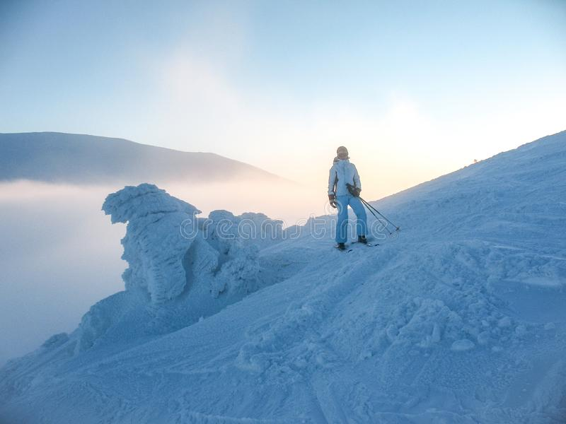Skier girl in blue jumpsuit on blue slope near the icy snowdrift. Mountain winter landscape in the Carpathians in Ukraine royalty free stock images
