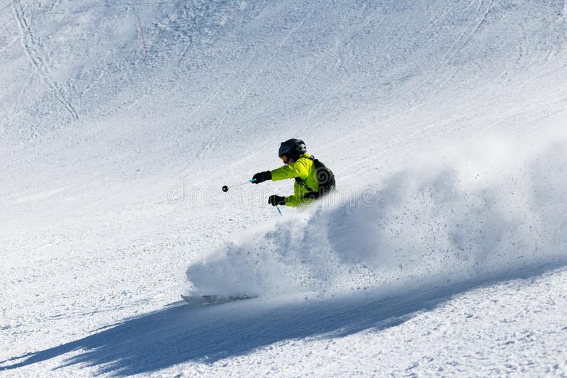 A skier at high speed descends from the mountain. stock photography