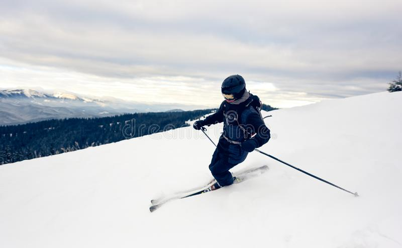 Skier inclining turning on snow-capped mountain peak. Extreme skiing concept. Mountains view. Grey sky on background. Professional male skier inclining down royalty free stock photo