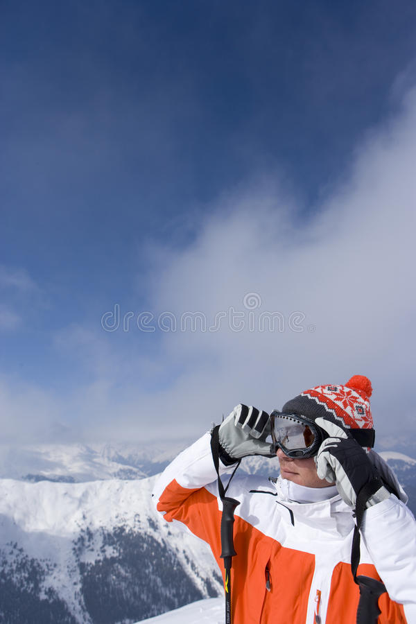 Skier on mountain top adjusting goggles stock photography