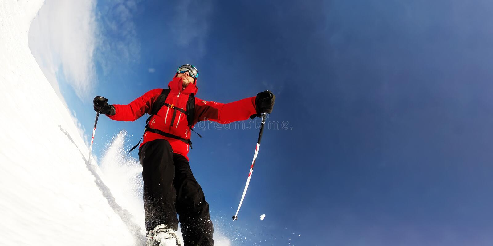 Skier in mountains performs a high speed turn on a ski piste royalty free stock photography