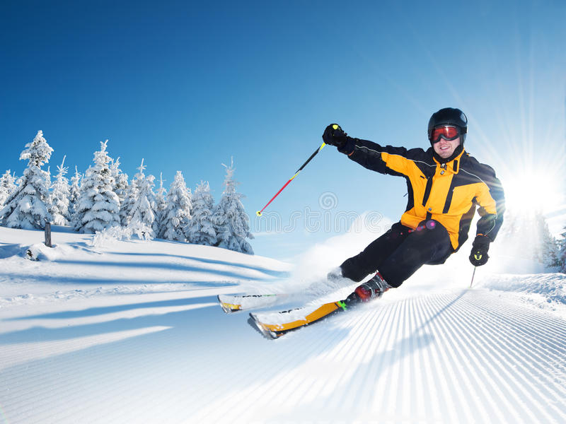 Skier in mountains, prepared piste and sunny day stock photos