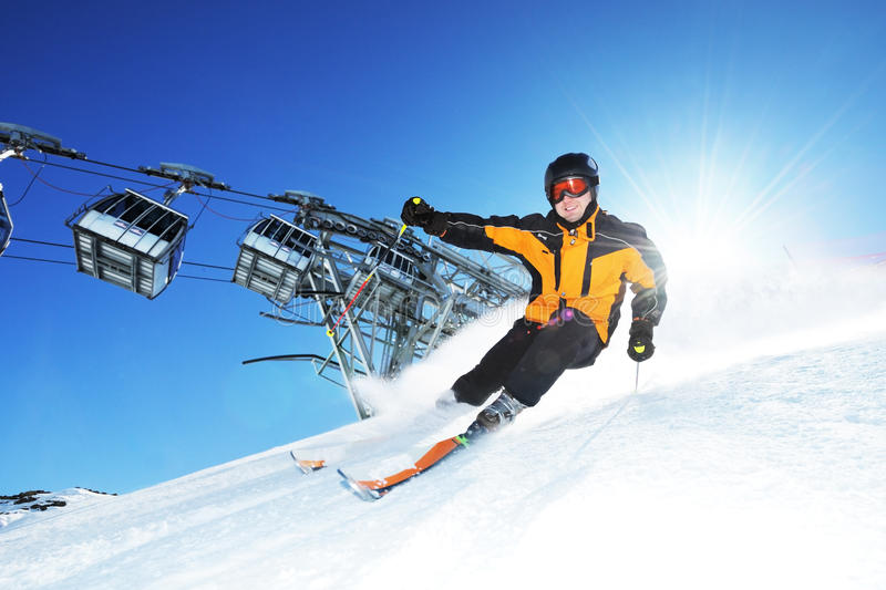 Skier in mountains, prepared piste and sunny day stock images