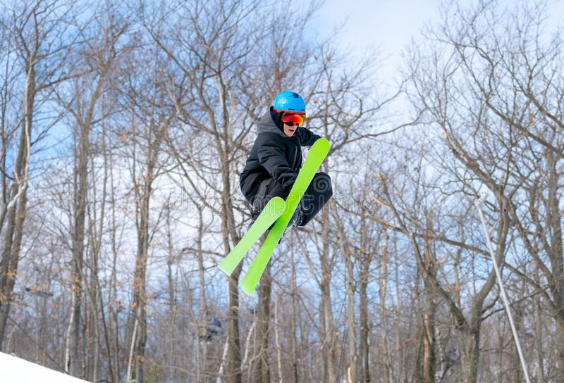 A skier performs a mid-air grab in a terrain park stock image