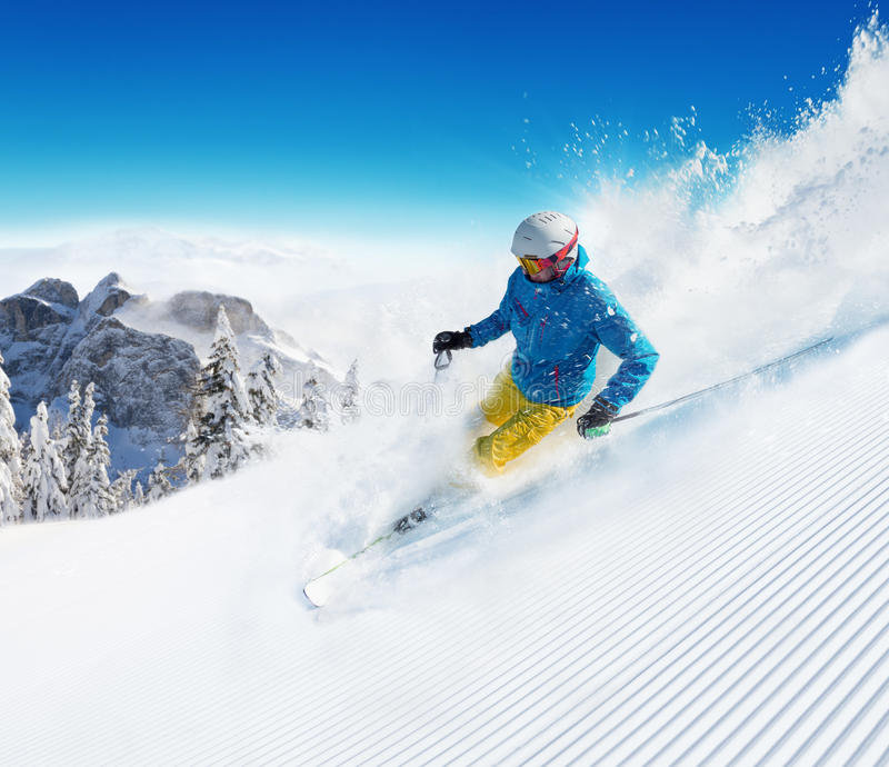 Skier on piste running downhill. In beautiful Alpine landscape. Blue sky on background. Free space for text stock photo