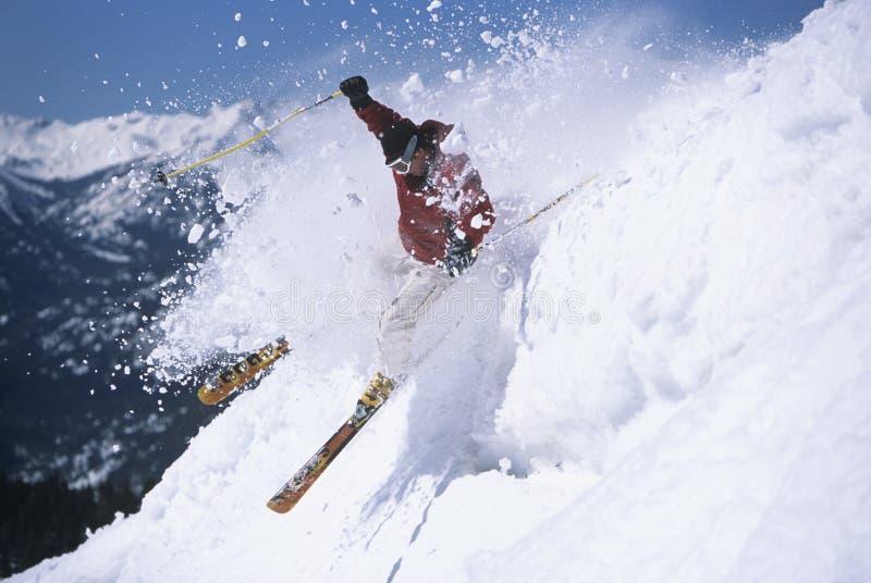 Skier Through Powdery Snow On Ski Slope. Side view of a male skier skiing through powdery snow on ski slope stock photo
