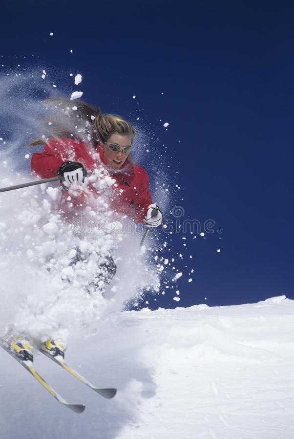 Skier Through Powdery Snow On Slope. Female skier skiing through powdery snow on ski slope against clear blue sky royalty free stock images