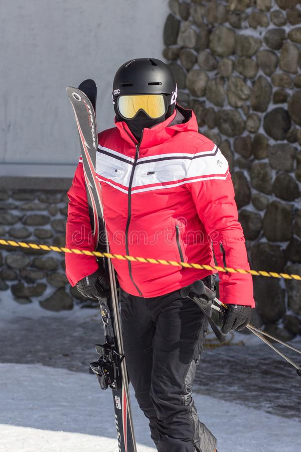 A skier in red jacket is holding his snowboard and ski poles. It is winter and the skier is standing on snow stock photo