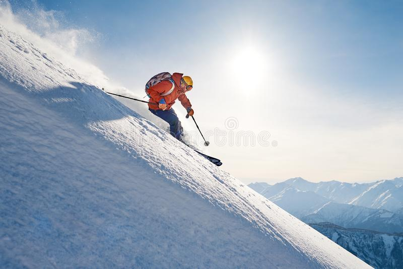 skier rides freeride on powder snow down slope against the backdrop of the mountains stock image