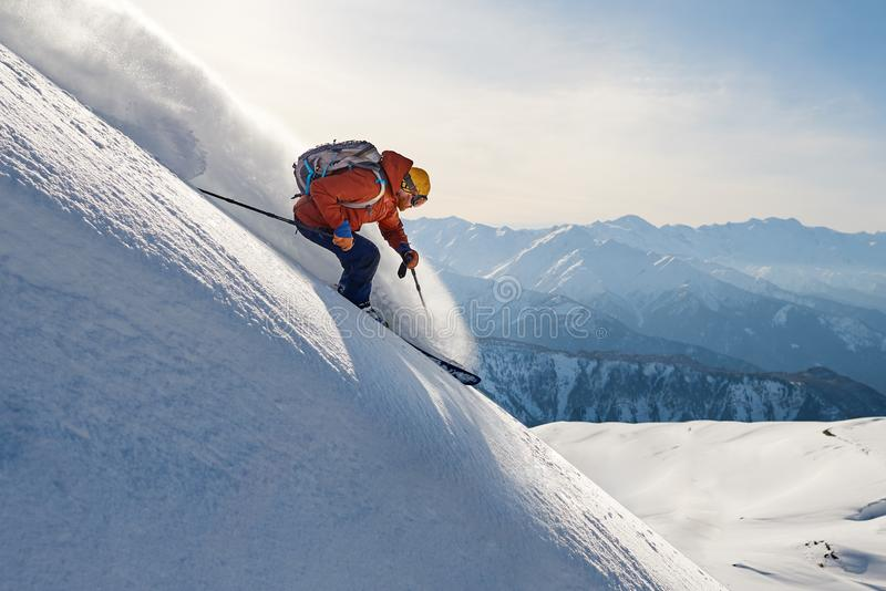 Skier rides freeride on powder snow down slope against the backdrop of the mountains. Skier rides freeride on powder snow down the slope against the backdrop of royalty free stock images