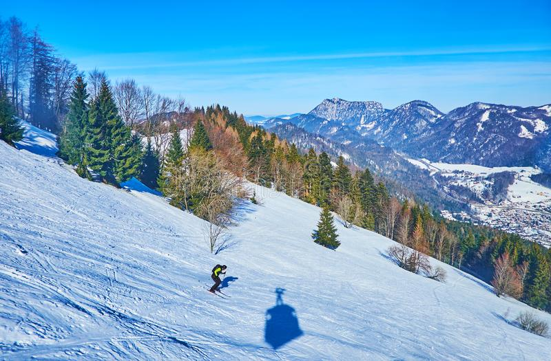The skier and shadow of cable car, Zwolferhorn, St Gilden, Salzkammergut, Austria. The skier makes the downhill along the piste of Zwolferhorn mount, that royalty free stock photo