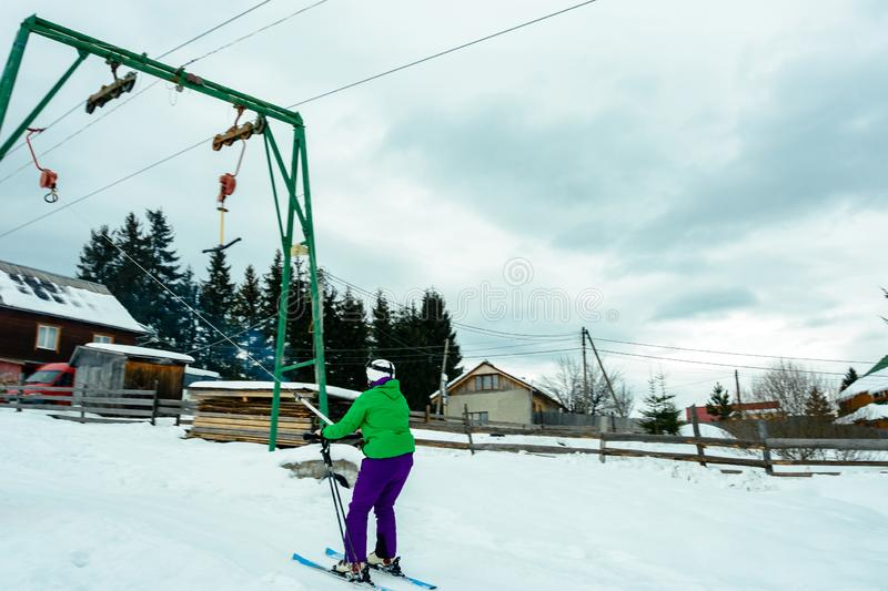The skier in the equipment rises to the mountain on a lift in the Ukrainian Carpathians royalty free stock image