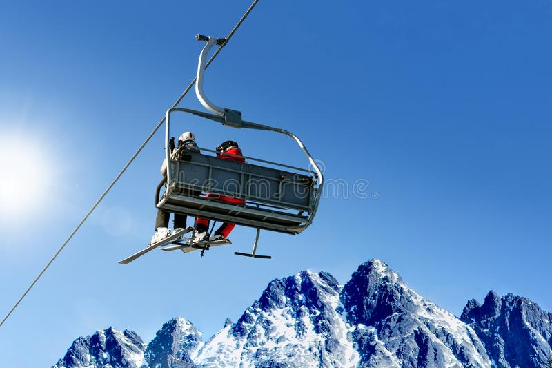 Skier sitting at ski lift. Skiers on a ski lift in high mountains on the background of a clear blue sky with copy space stock image