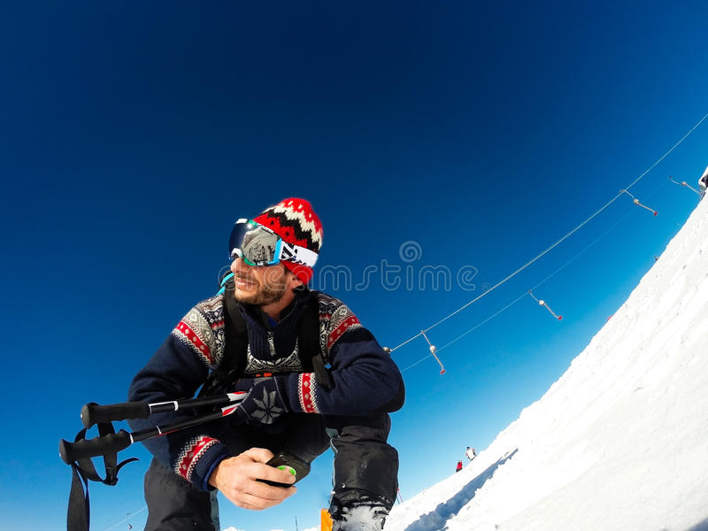 Skier sitting waiting to start skiing stock photography