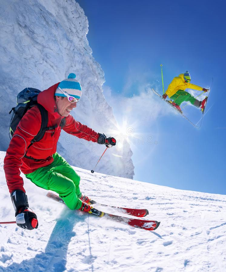 Skier skiing downhill in high mountains against blue sky royalty free stock images