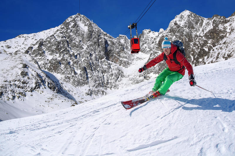 Skier skiing downhill in high mountains against cable lift. Colorful Skier skiing downhill in high mountains royalty free stock photography