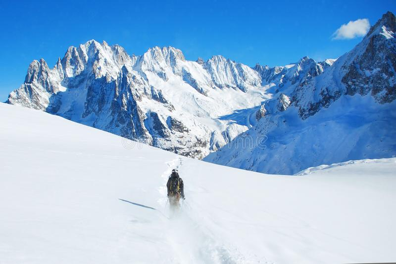 Skier skiing downhill in high mountains against sunshine royalty free stock photography