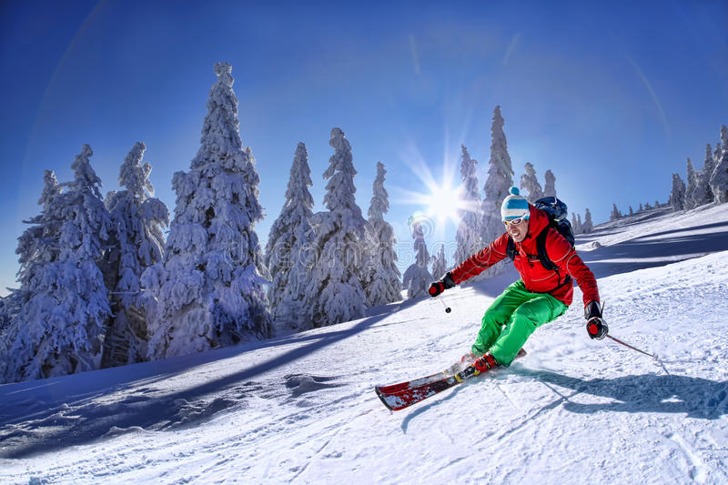 Skier skiing downhill in high mountains. Colorful Skier skiing downhill in high mountains royalty free stock image