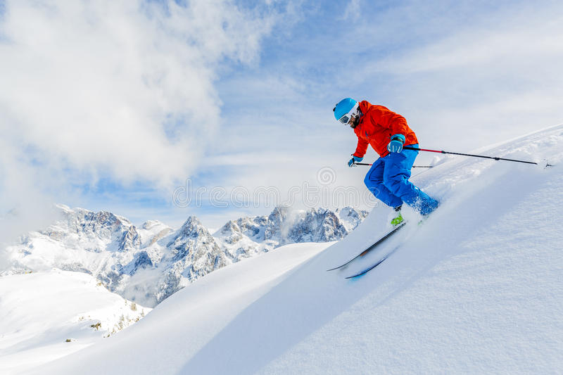 Skier skiing downhill in high mountains. stock photo