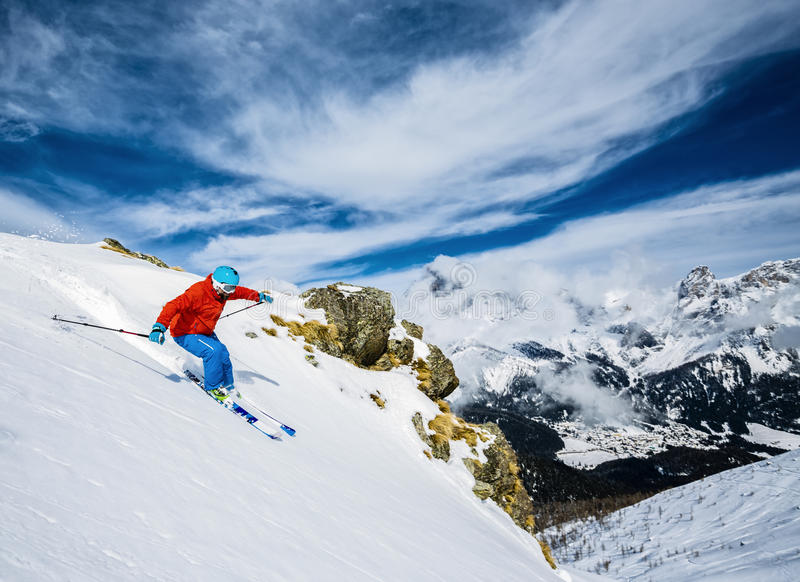 Skier skiing downhill in high mountains. Skier skiing downhill in high mountains in fresh powder snow. San Martino di Castrozza in Italy royalty free stock images