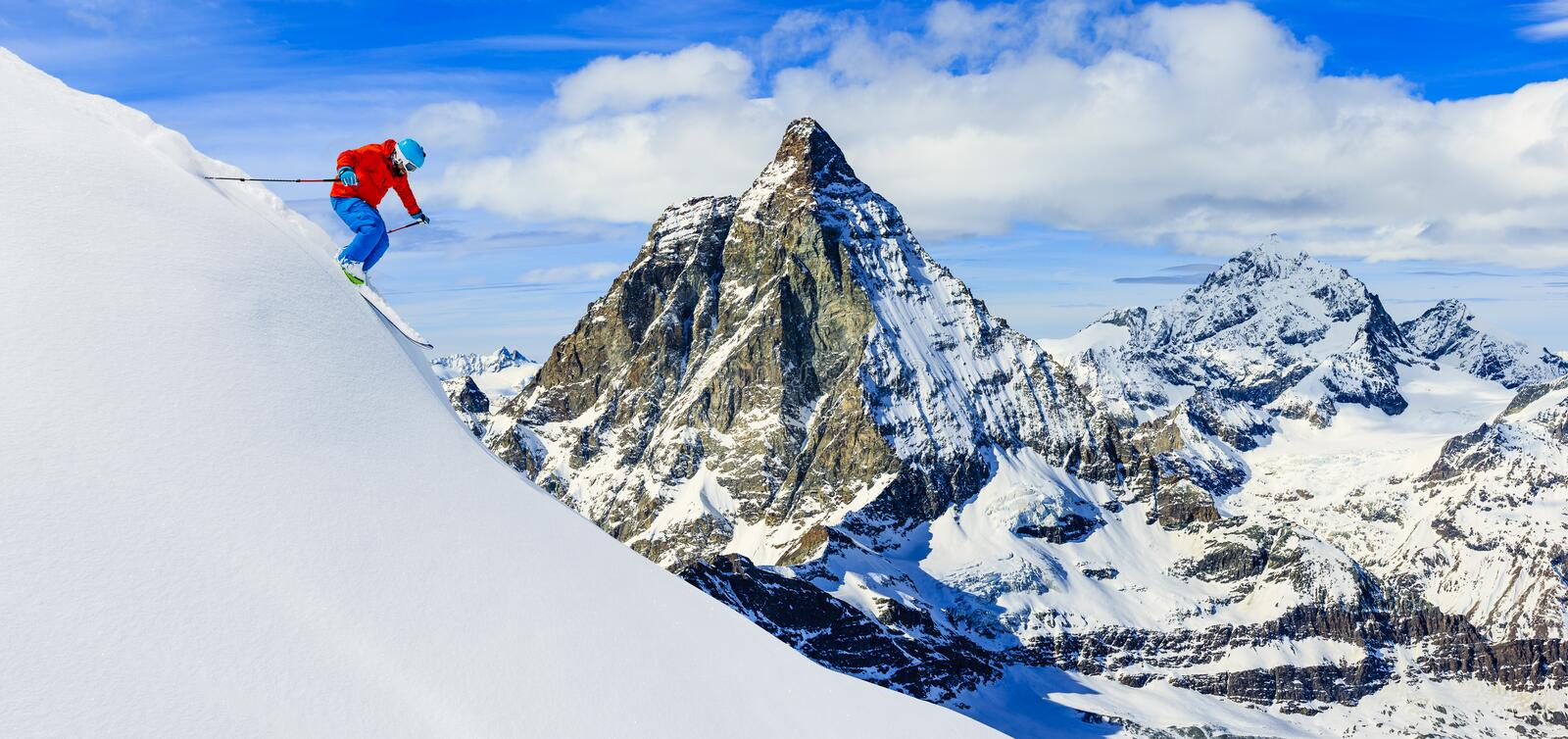 Skier skiing downhill in high mountains in fresh powder snow. Sn. Ow mountain range with Matterhorn in background. Zermatt Alps region Switzerland stock photo