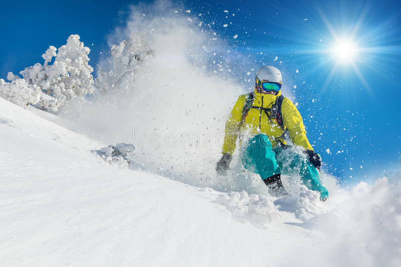 Skier skiing downhill in high mountains royalty free stock image