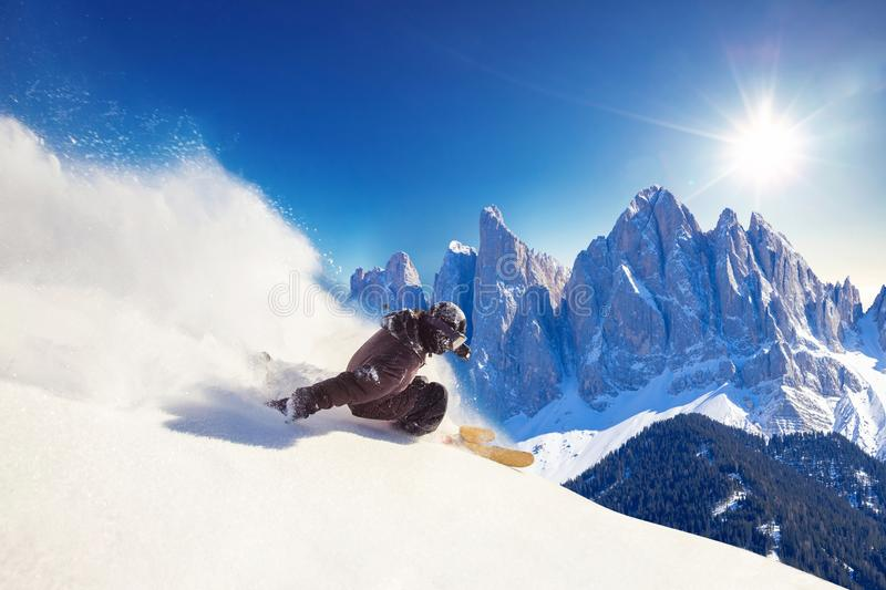 Skier skiing downhill during sunny day in Alps mountains and forest. Extreme winter sports royalty free stock image