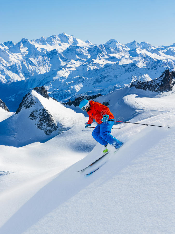 Skier skiing downhill Valle Blanche in french Alps in fresh powder snow. Snow mountain range Mont Blanc with Grand Jorasses in ba. Ckground stock images