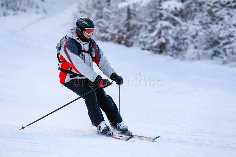 Skier skiing downhill in winter mountains royalty free stock image