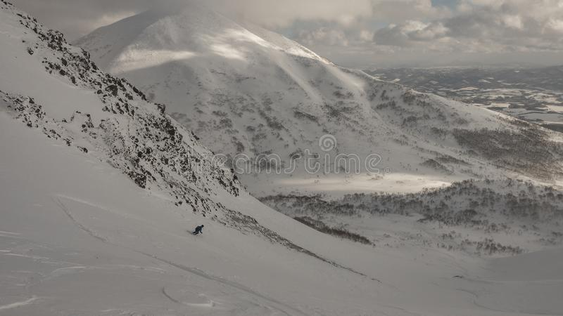 Skier skiing on mountain on a cloudy day stock photo