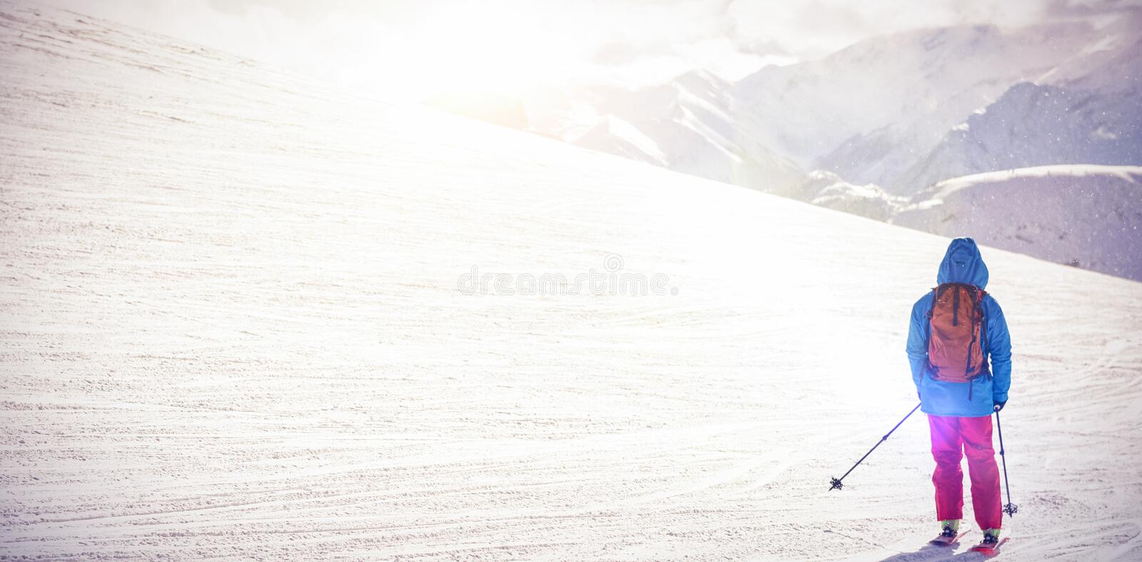 Skier skiing on snow covered mountains. Rear view of skier skiing on snow covered mountains royalty free stock photo
