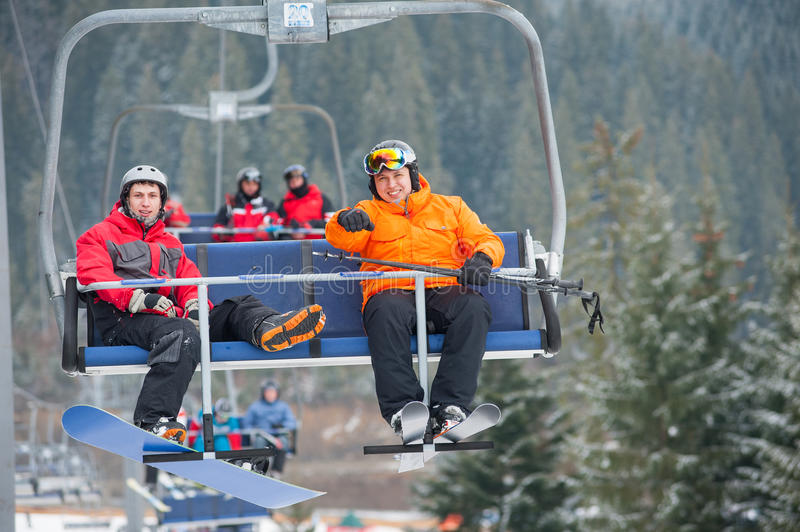 Skier and snowboarder riding up on ski lift. Skier and snowboarder riding up to the top of the mountain on ski lift, with an astonishing view nature. Bukovel stock image