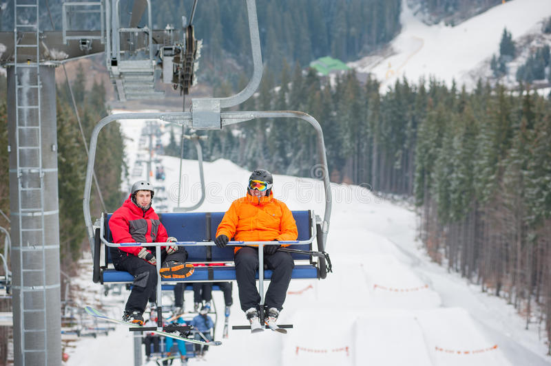 Skier and snowboarder riding up on ski lift. Skier and snowboarder riding up to the top of the mountain on ski lift, with beautiful view nature royalty free stock photo