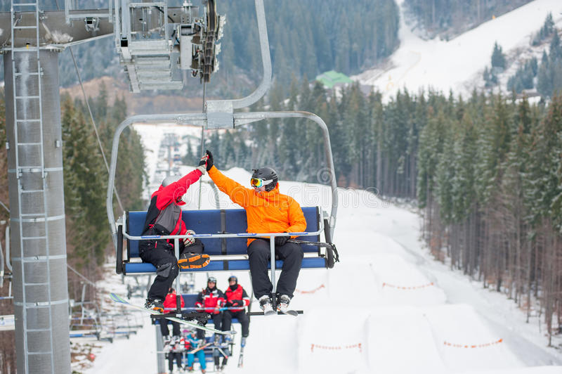 Skier and snowboarder riding up on ski lift. Two male ride the ski chair lift up the mountain together and giving each other a high five, having a fun time stock image