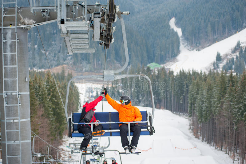 Skier and snowboarder riding up on ski lift. Two male ride the ski chair lift up the mountain together and giving each other a high five, having a fun time royalty free stock photography