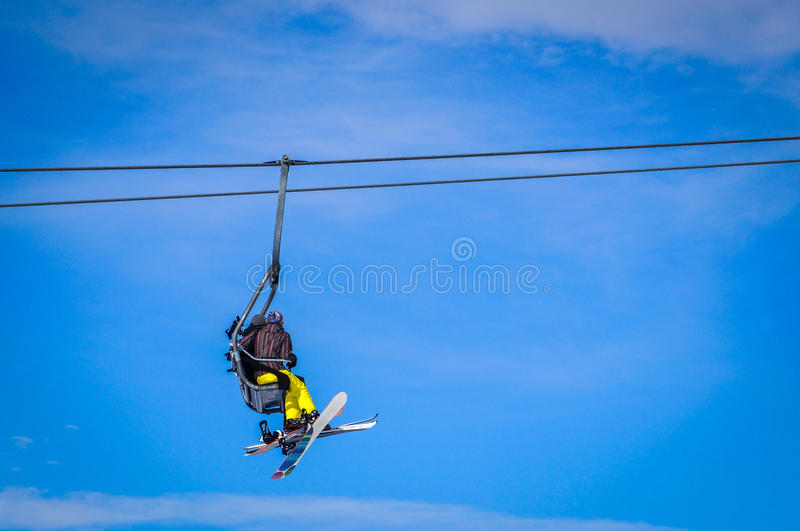 Skier and snowboarder sitting in ski lift. In high mountains. Blue sky background. Place you text stock photo