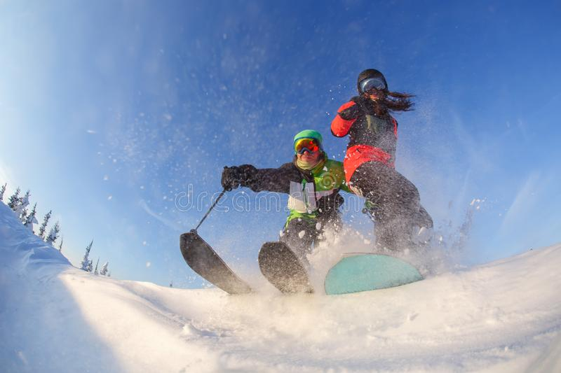 Skier and snowboardgirl on the background of blue winter sky royalty free stock photo