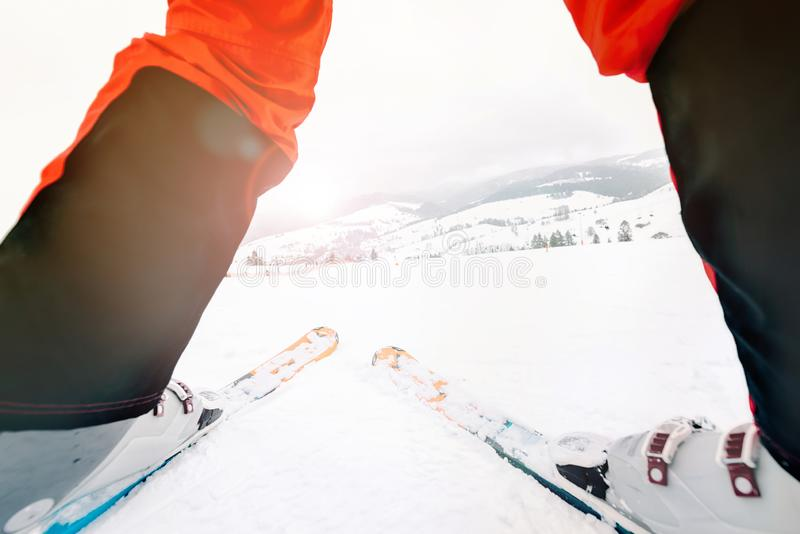 Skier standing in front of white ski slope - winter sport concept with skier on top of the mountain ready to ride down stock photography
