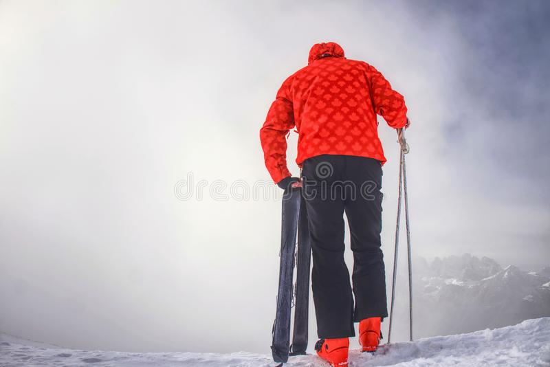Skier stay with skis on mountain edge above deep slope valley royalty free stock photos