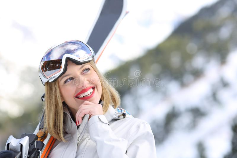 Skier thinking looking at side in winter holiday. Happy skier thinking looking at side in winter holiday in the mountain royalty free stock image