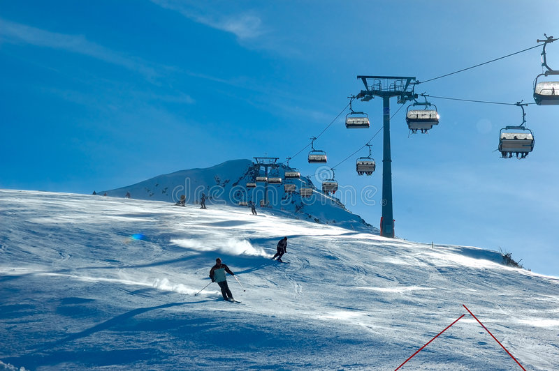 Skiers on chair lift. Blue sky royalty free stock images