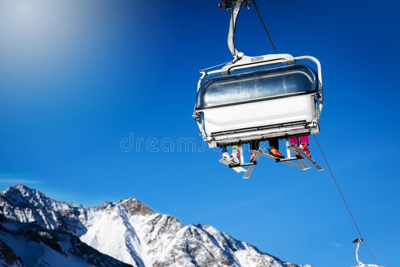 Skiers in a chairlift against blue sunny sky at ski resort. In Italy Alps stock photography