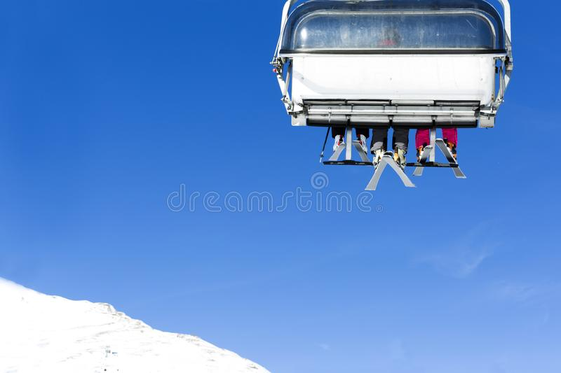 Skiers going up on the chairlift against bright blue sky- ski re. Sort in Italy on sunny winter day stock photography